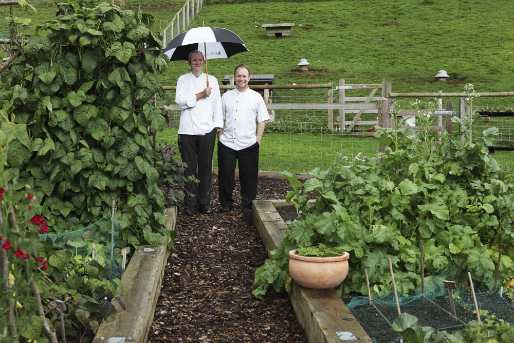 Two chefs in a garden sharing an umbrella