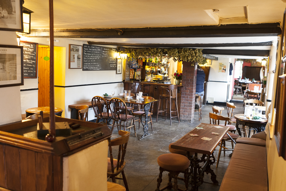 The interior of the Red Hart Inn, Blaisdon. There is wooden furniture and tiled floors. It is cosy and welcoming.