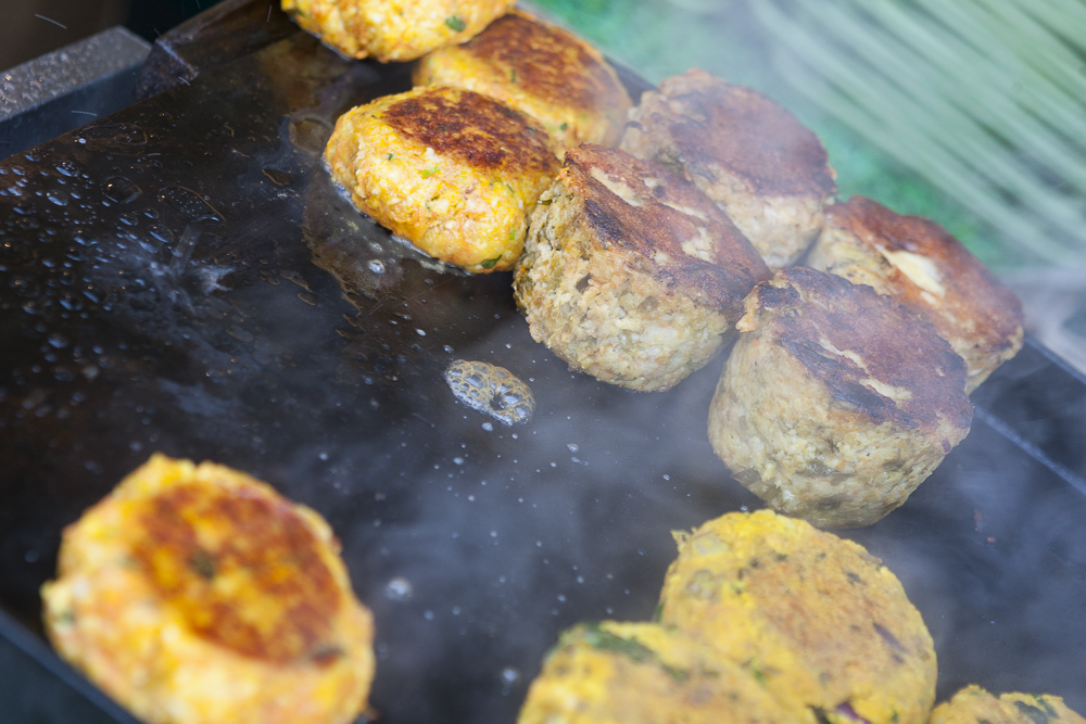 Mouthwatering vegetarian patties sizzling on a griddle.