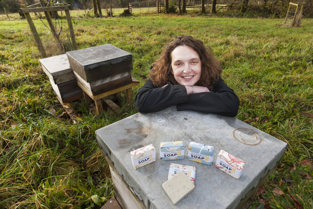 Sarah gates sitting in a field in front of a bee hiveand her amazing soaps on display