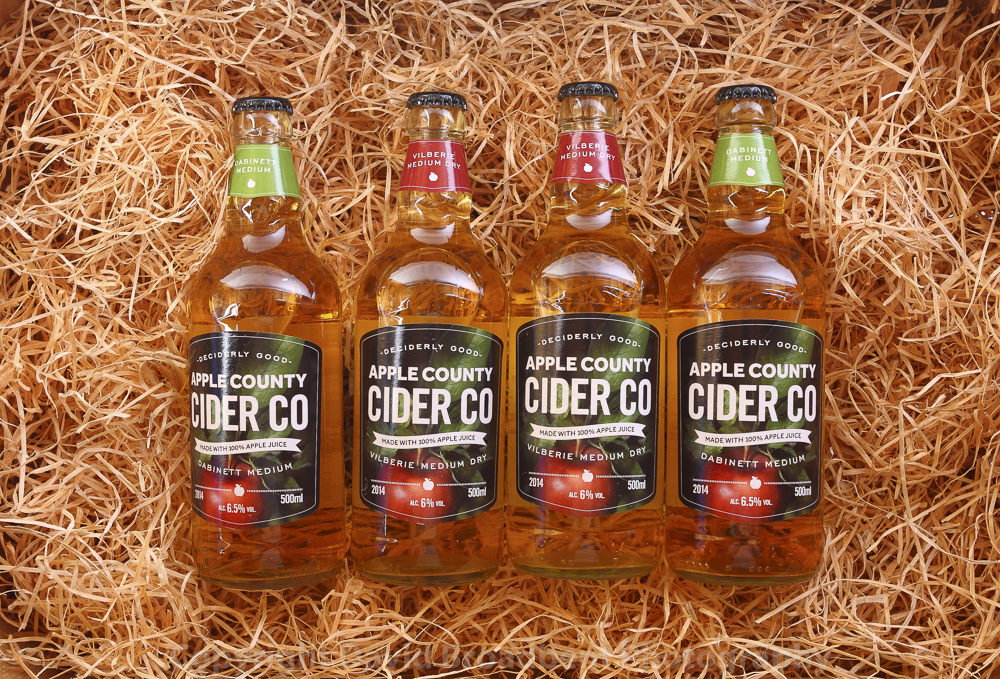 Bottles of Apple County Cider displayed against some hay.